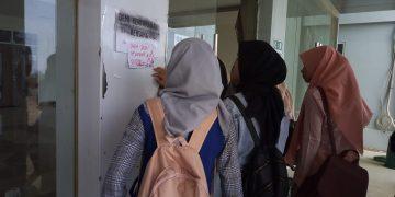 Mahasiswa berkerumun membaca kertas coretan protes yang dipasang di Gedung baru ISdb, Rabu (16/10/2019) (Amanat/Rani).