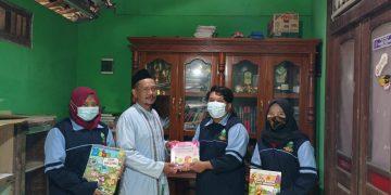 Mahasiswa KKN menyerahkan buku bacaan kepada penanggung jawab taman baca di Desa Sukolilan, Kabupaten Kendal. Minggu (21/02/2021).