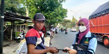 Mahasiswa KKN MP UIN Walisongo sedang membagikan masker kepada warga di depan Kampus 3. Minggu, (09/05/2021)(Amanat/Anisa Alfath).